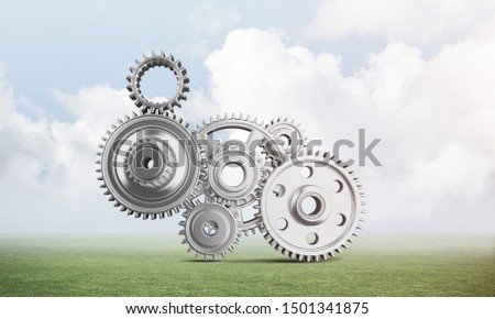 Abstract mechanism with cogwheels on green meadow. Construction and manufacturing. Mechanical technology machine engineering. Nature landscape with green grass and blue sky. Mixed media with 3D object