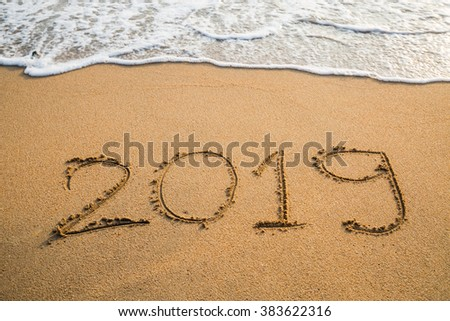 Abstract message Year 2019 written on beach sand background #383622316