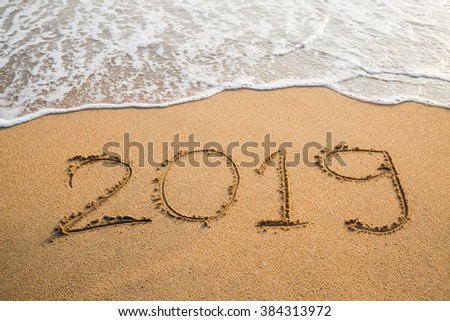 Abstract message Year 2019 written on beach sand background #384313972