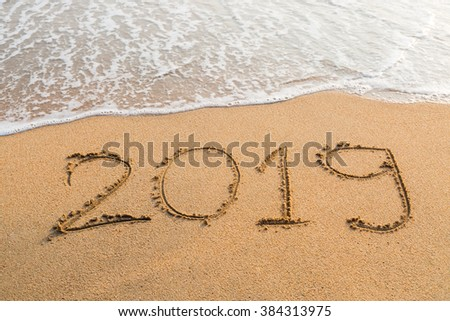 Abstract message Year 2019 written on beach sand background #384313975
