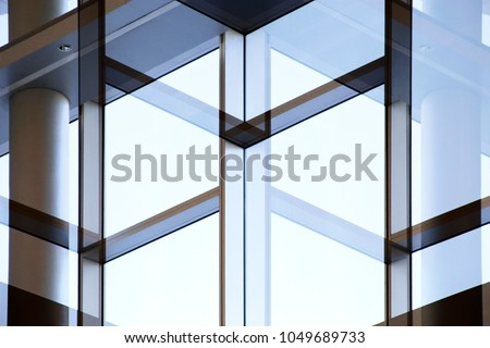 Abstract modern architecture background. Column / pillar and glass wall with metal framework. Structural glazing. Reworked photo of transparent wall with against clear blue sky. #1049689733