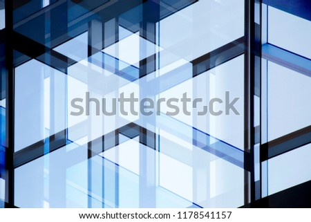 Abstract modern architecture background in shades of blue color. Double exposure photo of glass wall with metal framework. Structural glazing. Fragment of office building fragment against clear sky.