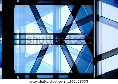 Abstract modern architecture background. Structural glazing. Reworked close-up photo of office building fragment in shadows against clear blue sky. Glass wall with steel or aluminum framework. #1166569333