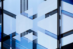 Abstract modern architecture. Double exposure photo of glass wall with metal framework. Structural glazing. Fragment of office building with clear blue sky.