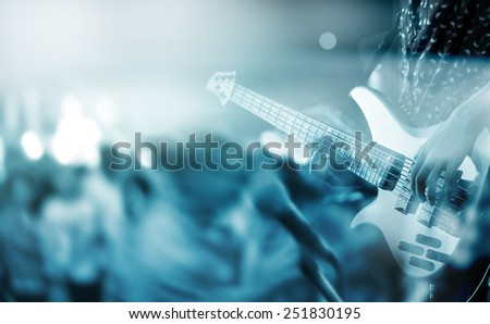 abstract motion blur guitarist on stage and people dance in floor, blue tone and blur concept