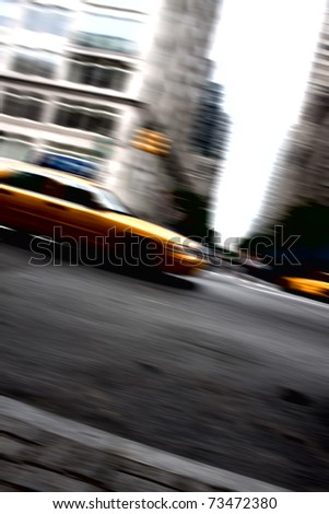 Abstract motion blur of a city street scene at night with a yellow taxi cab speeding by.