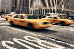 Abstract motion blur of a city street scene with a yellow taxi cabs speeding bY