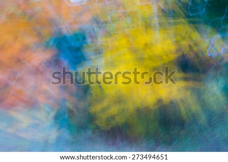 Abstract motion blur of fall colored trees.  Yellow and orange are blurred for a blur background affect.