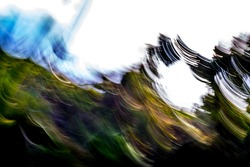 Abstract, motion-blurred, shades of green and yellow mountainside under blown-out sky background texture