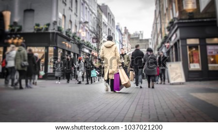 Abstract motion blurred shopper carrying shopping bags on crowded London street  #1037021200