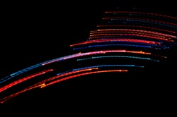 Abstract multicolored light beams in motion, light painting on a black background. Rainbow