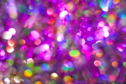 Abstract multicolored purple rainbow background. Defocused light holographic tinsel with bokeh effect.