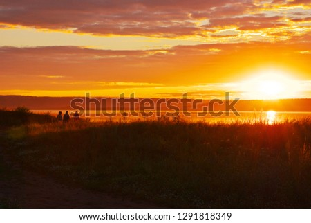 Abstract nature background. Dramatic and moody pink, purple, yellow, golden and blue cloudy sunset sky. Beautiful nature dusk scene. Group of people silhoettes sitting on beach enjoying the sunset. #1291818349