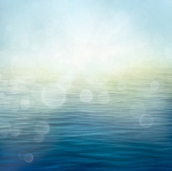Abstract nature summer or spring ocean sea background. Small waves on water surface in motion blur with bokeh lights from sunrise.