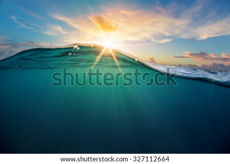 Abstract ocean design template with underwater part and sunset skylight splitted by waterline. Beautiful clouds and bright sun over sea water.