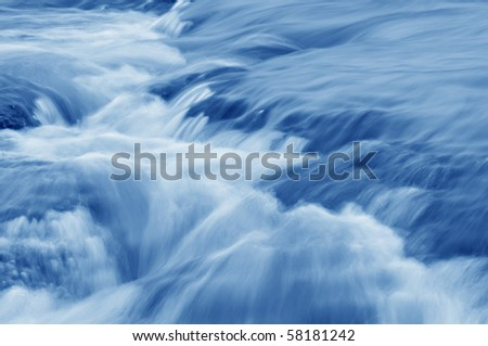 Abstract of a swiftly moving stream in shade of blue.
