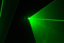 Abstract of digital green light laser line, disco light show, stage lights with laser.Green laser beams light effect on black background.Green light beam from lens projector on black background