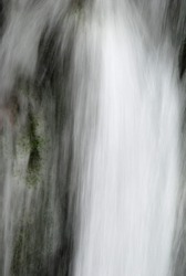 Abstract of fast moving water pouring over a mossy waterfall