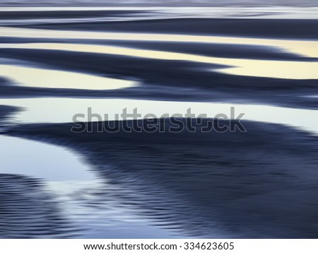 Abstract of luminous tide pools on sandy beach at sunset along the Pacific coast of Olympic Peninsula in Washington, USA, for themes of nature, serenity, the environment (one of a series)