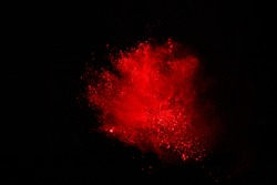 Abstract of red powder explosion on black background. Red powder splatted isolate. Colored cloud. Colored dust explode. Paint Holi.