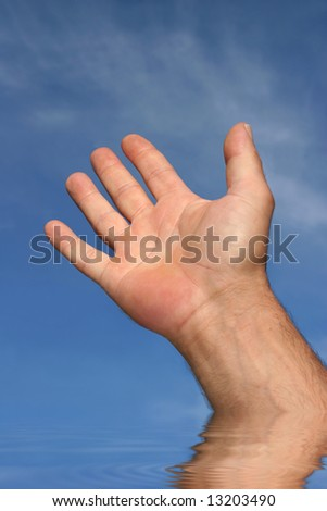 Abstract of the hand of a man reaching towards a blue sky with reflection in rippled water.