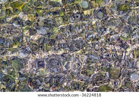 Abstract of the shallow water   with light scatter from the pebbles in the crystal clear water. Makes an excellent computer screen background. - stock photo