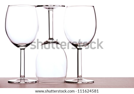 Abstract of three empty wine glasses backlit against white background.