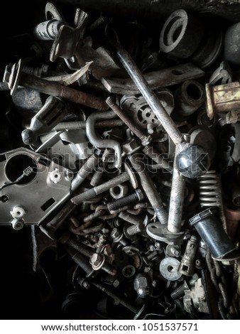 Abstract of Used Metallic for Background of Used old and dirty spare parts wait for get rid or sell to recycle Rusty nuts and bolts background.Dark HDR Grain Tone Style. #1051537571