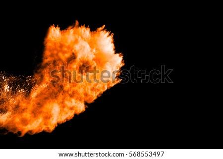abstract orange powder splatted on black background,Freeze motion of orange powder exploding/throwing  powder.