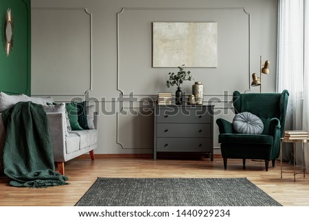 Abstract painting on grey wall o contemporary living room interior with emerald green armchair with round pillow, commode and couch
