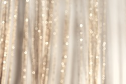 Abstract pastel blurred background. Mysterious Christmas defocused background. Festive frame with twinkling bokeh stars. Abstract blurred bokeh curtain.Tender background in milky gray tones.