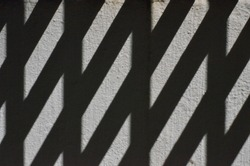 Abstract pattern formed by the shadow odf a fireescape on a grey wall