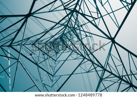 Abstract pattern from bottom view of high voltage pole power transmission tower with clear sky sunny day background in monochrome tone. Green energy, environmental conservation concept. #1248489778