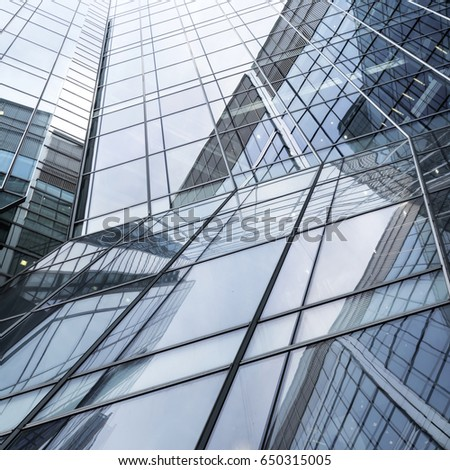 abstract pattern of lines and sky reflecting glass facades of modern steel corporate building #650315005