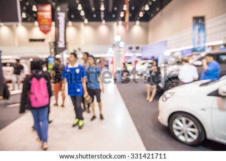Abstract people walking in motor show blurred defocusing background. Concept of business social gathering for meeting exchange.