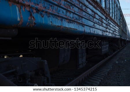 Abstract perspective background - old scary shabby blue passenger train. The train-ghost cars perspective photo. Terrible train. Old decommissioned train in a disgusting state. Old sprinkled paint.