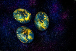 Abstract photo of eggs on galaxy glitter dark background. Easter cosmic space colored eggs. Idea for greetings and Easter. Top view concept with colored eggs in flat lay style. High quality photo