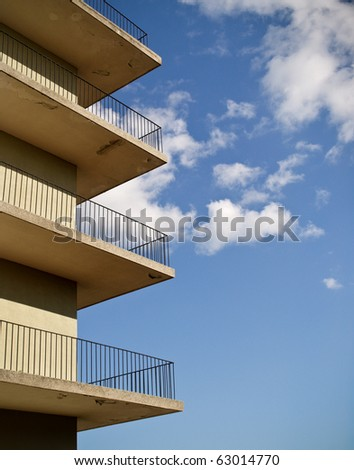 abstract photo of four minimalistic identical balconies against a blue sky.