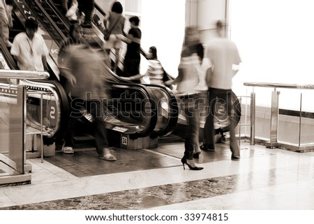 Abstract photo of people moving on escalator in the shopping mall(signs on escalator - bowling, karaoke)