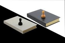 Abstract photo with chess pieces on books, black pawn on light book and white background, white pawn on dark book and white background as symbol of opposition and struggle