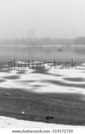 Abstract photograph of a stylized old style with blur and noise in a snow storm on the first ice of the lake with garbage and bottles and fishermen on boats in front of buildings in the fog. #519571750