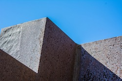 Abstract Photography. Part of the wall contrasting with the sky. Contrast of color and texture. Angles, straight lines.