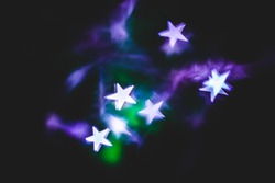 Abstract Photography with Star Shaped Lights with Purple and Green Colors on the Background