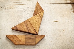 abstract picture of a sailing boat built from seven tangram wooden pieces over a rustic white painted barn wood