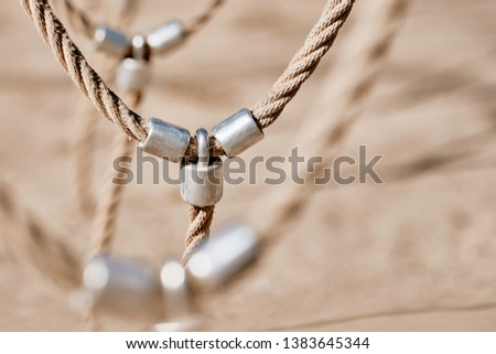 Abstract picture shot on a playground at a climbing frame with a detail with bright beige ropes connected via metal. Seen in Nuremberg, Germany, April 2019 #1383645344