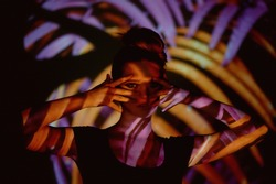 Abstract portrait of a beautiful girl in the light of the projector. Purple and orange colors. Alien jungle. Beautiful, dangerous and mysterious