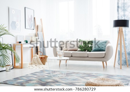 Abstract posters hanging on a bright white wall facing a comfy sofa in a bohemian style day room interior #786280729