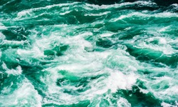 Abstract powerful water currents and rapids churning in flowing green river near Niagara Falls, Ontario, Canada.