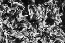 Abstract puffs of natural black smoke and white huge flame of strong fire. Black and white photography, motion blur from fire, high temperature from flames. Dangerous firestorm abstract background.