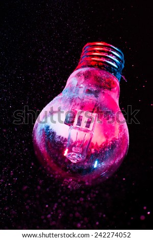 Abstract Purple colorful light bulb with powder on black background